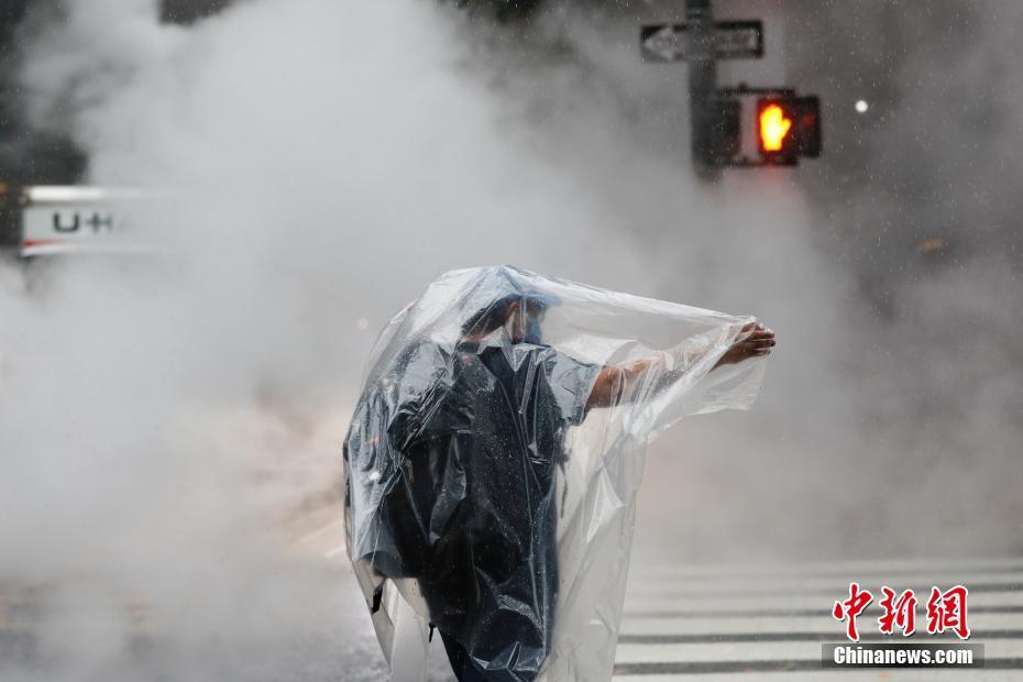 美国纽约降下暴雨 行人身披塑料布出行