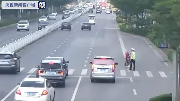 赞!广西玉林一老人过马路 车辆集体停让无催促 辅警小心搀扶
