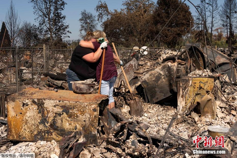 美国山火过下民众重回家园 母女二人在废墟上相拥