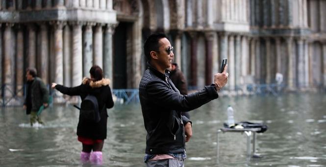 威尼斯水灾持续 民众站水中淡定拍婚纱照玩自拍