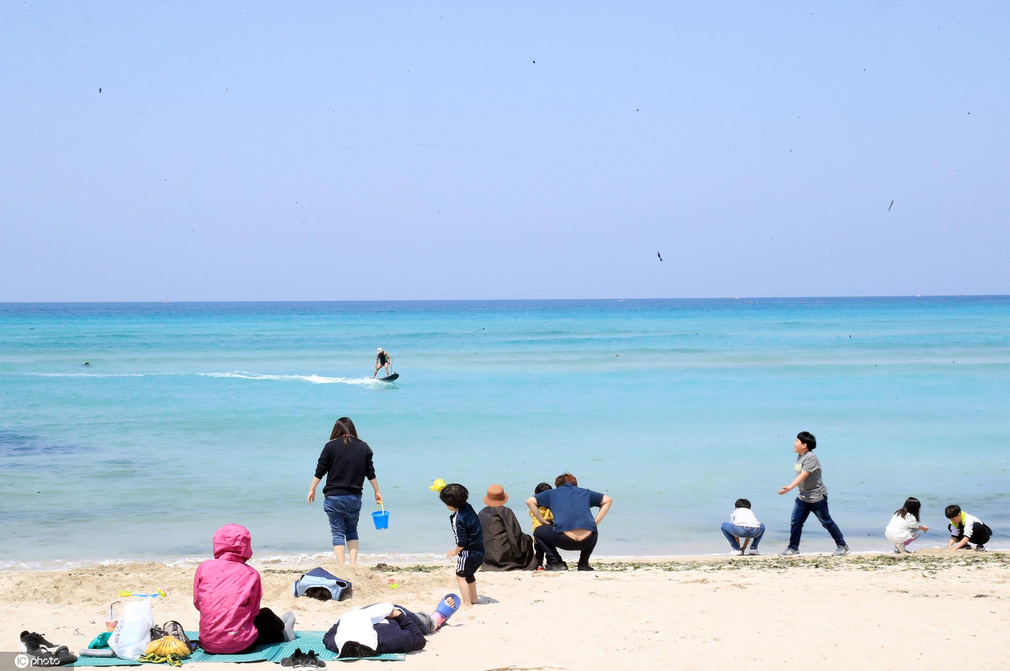 韩国济州岛天气转暖?游人在海水浴场冲浪